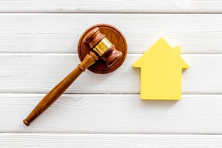 Inheritance of the house concept with figure and gavel on white wooden background top view