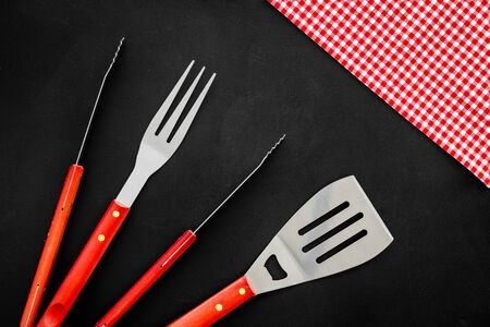 set of used barbecue tools on black background top view