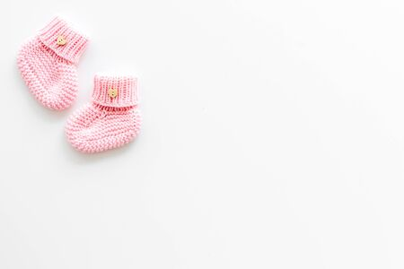 Pink knitted footwear for kids on white background top view space for text Stockfoto