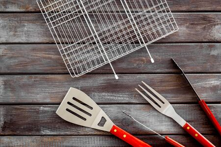 set of used barbecue tools on wooden background top view