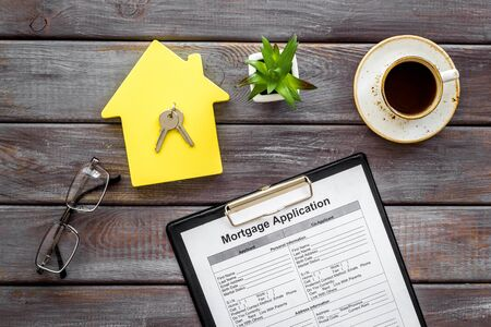 House mortgage with application, house toy, keys, glasses, coffee on wooden banker desk background top view Stok Fotoğraf - 129786203