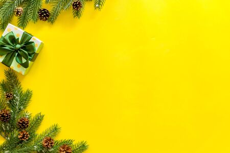 Boxes with presents and fir tree frame for christmas on yellow background top veiw mockup