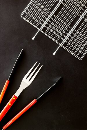 Grid, tongs, fork, spatula for barbecue and grill on black background top view