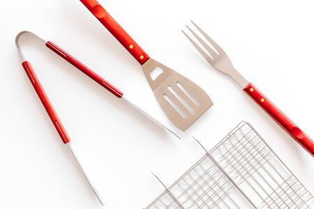 Grid, tongs, fork, spatula for barbecue and grill on white background top view 免版税图像