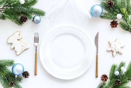 Christmas table setting with plate, fork, knife, fir tree and toys on white background top view