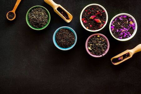 Assortment of dry tea in bowls frame on black background top view copyspace
