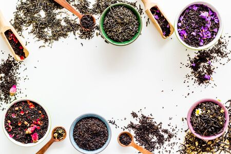 Assortment of dry tea in bowls frame on white background top view copyspace Фото со стока