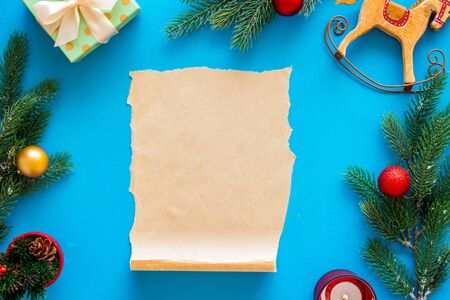 Letter to Santa Claus concept. Paper on blue background with New Year decoration top view mockup space for text Banque d'images - 129469662
