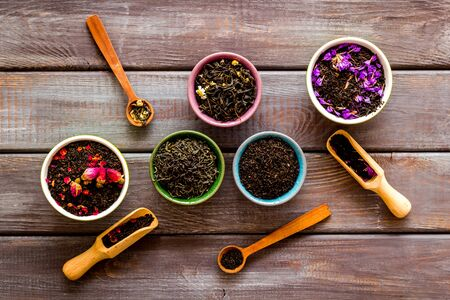 Assortment of dry tea in bowls on wooden background top view Фото со стока
