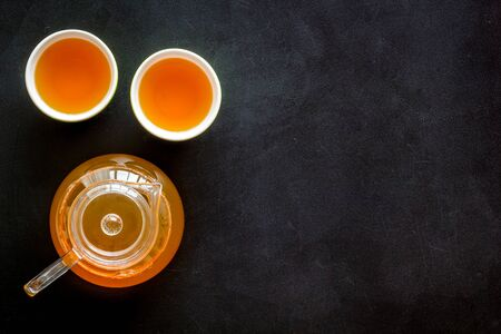 Tea brewing in pot and cups on black background top view space for text
