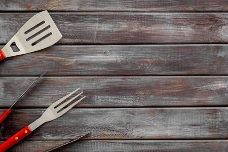Tongs, fork, spatula for barbecue and grill on wooden background top view copyspace