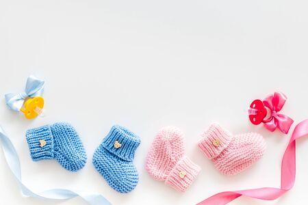 Blauw en roze gebreid schoeisel met dummy voor babyjongen en meisje op witte achtergrond bovenaanzicht mock up Stockfoto