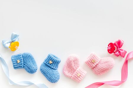 Blue and pink knitted footwear with dummy for baby boy and girl on white background top view mock up