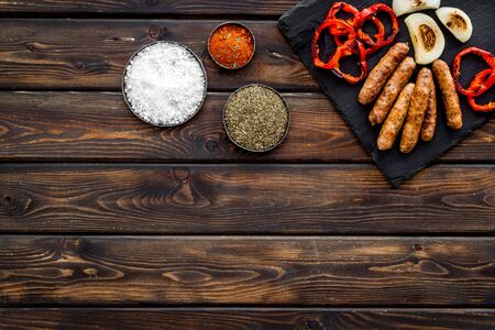 Barbecue set. Grilled sausages, vegetables on kitchen board and spices on wooden background top view mock-up