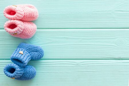 Knitted blue and pink footwear for baby boy and girl on mint green wooden background top view mock up Stock Photo - 129481151