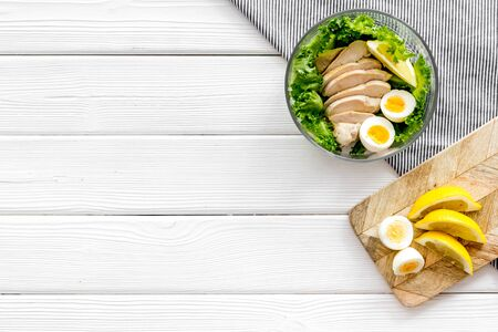 Salad bowl with healthy food for lunch at work place on white wooden background top view space for text