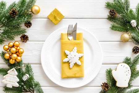 Christmas table setting with plate, fork, knife, fir tree and gift in box on white wooden background top view