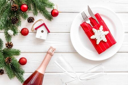 New year and chistmas eve. Table setting with spruce, plate, flatware on white wooden background top view