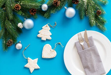 2020 year celebration with table setting, plate, fork, knife, spruce, ginger cookies on blue background top view Stockfoto