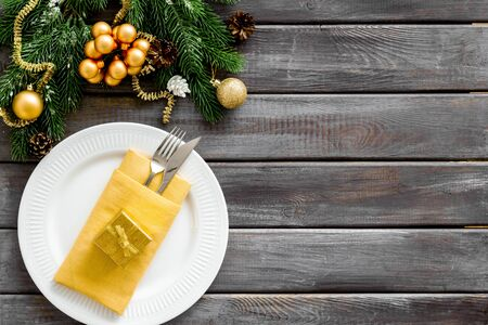 Christmas table setting with plate, fork, knife, fir tree and toys on wooden background top view space for text Stockfoto