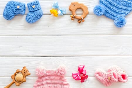 Blue and pink knitted set for kids, rattle, dummy on white wooden background top view space for text