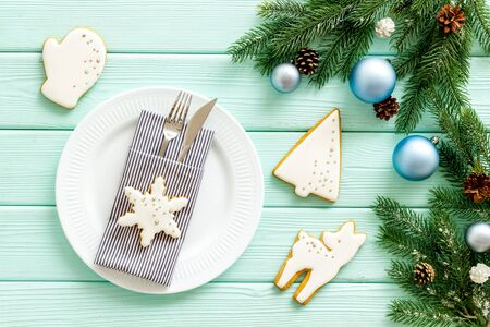 New year and chistmas eve. Table setting with spruce, plate, flatware on mint green wooden background top view