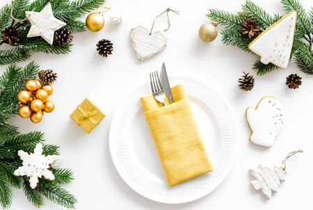 Christmas table setting with plate, fork, knife, fir tree and gift in box on white background top view