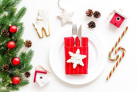 Table setting for new year 2020 celebration with pine branch, decorations, candy cane, plate and tableware on white table background top view