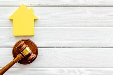 Inheritance of the house concept with house figure and inscribed gavel on white wooden background top view space for text