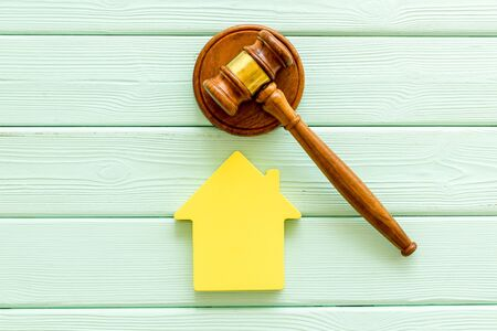 Inheritance of the house concept with house figure and inscribed gavel on mint green wooden background top view Banco de Imagens