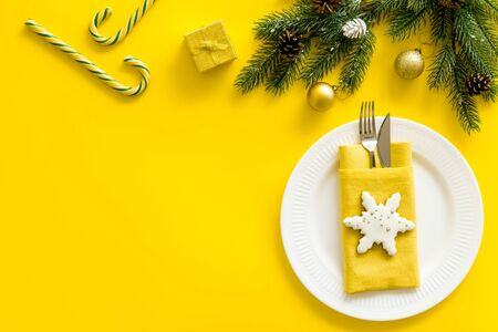 Christmas table setting with plate, fork, knife, fir tree and gift on yellow background top view space for text