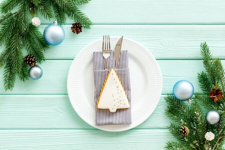 Christmas table setting with plate, fork, knife, fir tree and toys on mint green wooden background top view