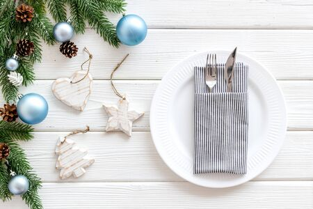 Table setting for new year 2020 celebration with pine branch, decorations, plate and tableware on white wooden table background top view