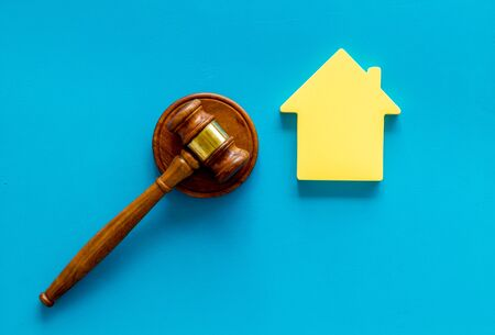 Inscribed gavel, house figure for inheritance concept on blue background top view.