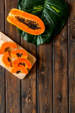 Papaya slices on cutting board near tropical leaves top view. Banque d'images - 129475103