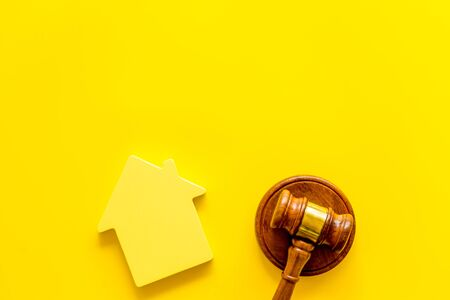 Inheritance of the house concept with house figure and inscribed gavel on yellow background top view space for text