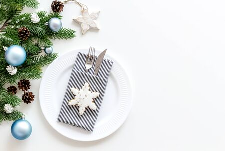 Christmas table setting with plate, fork, knife, fir tree and toys on white background top view space for text Stockfoto