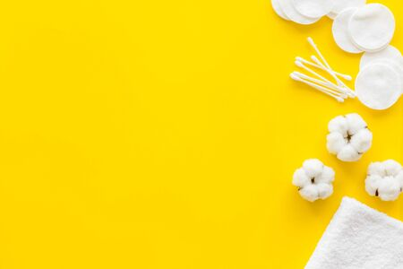 Cotton flowers with pads and swabs on yellow background top view mock up Stock Photo
