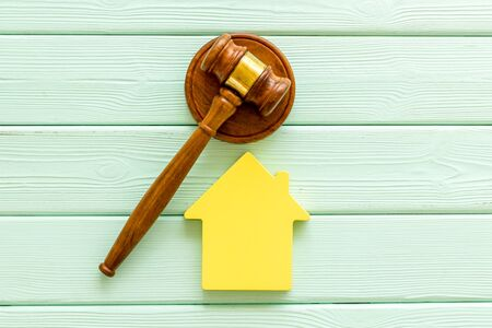 Inheritance of the house concept with figure and gavel on mint green wooden background top view