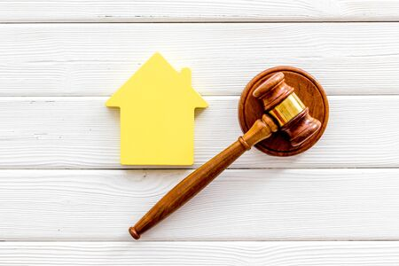 Inheritance of the house concept with house figure and inscribed gavel on white wooden background top view