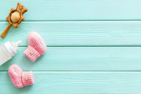 Pink knitted footwear and rattle, bottle for baby on mint green wooden background top view mock up