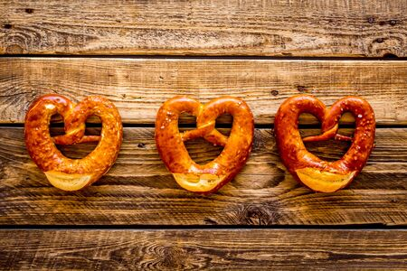 October fest symbol. Fresh pretzels on rustic wooden background top view copy space Stock fotó