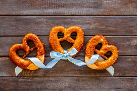 Octoberfest symbol. Fresh bavarian pretzels on dark wooden background top view Stock Photo