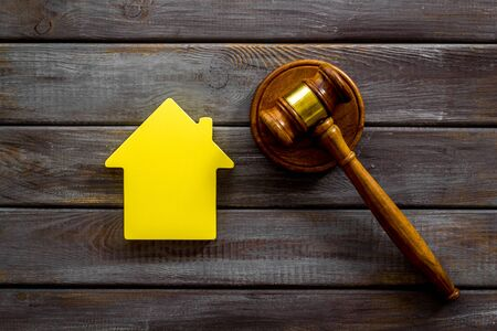 Inheritance of the house concept with figure and gavel on wooden background top view