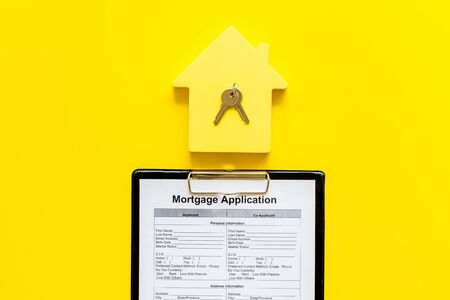 Mortgage application with house figure and keys on yellow background top view