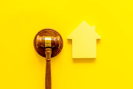 Inheritance of the house concept with figure and gavel on yellow background top view