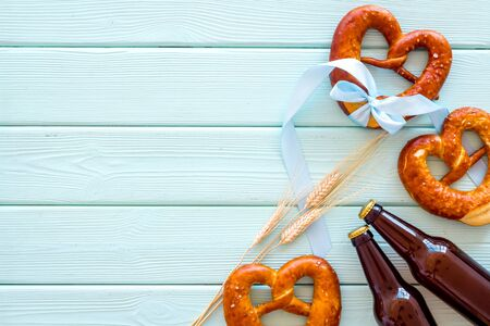 Octoberfest frame. Pretzels and beer on blue wooden background top view copy space