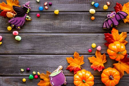 Nice halloween background with sweets. Cookies and pumpkins on dark wooden top view frame copy space Imagens