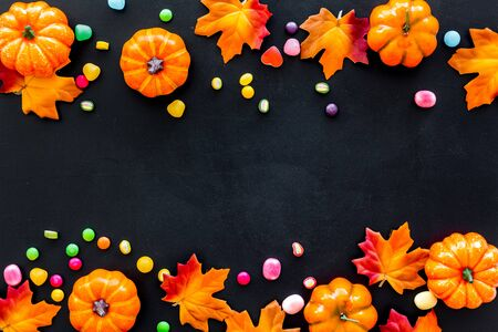 Bright Halloween composition with sweets and pumpkins on black background top view.
