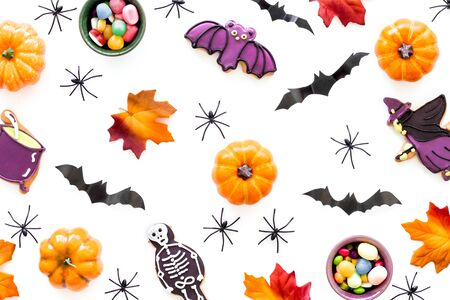 Nice halloween background with sweets. Cookies and pumpkins on white top view. Stok Fotoğraf